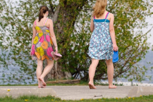 Two women wear floral-print dresses and carry their flip-flops as they walk barefoot along the Howard Temin Lakeshore Path near Lake Mendota at the University of Wisconsin-Madison during spring on May 10, 2011. The area is part of UW-Madison's Lakeshore Nature Preserve.