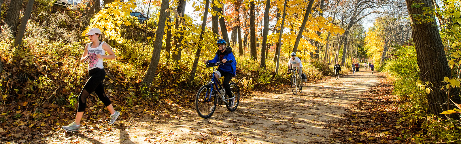 Pedestrians ride their bicycles and walk on a colorful tree-lined path at the Howard Temin Lakeshore Path during fall at the University of Wisconsin-Madison on Nov. 4, 2016.