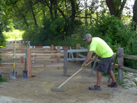 A grounds worker smooths the surface material on the path at the entrance to Picnic Point with a rake.