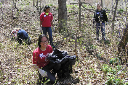 A smiling student volunteer is kneeling with a black trash bag in the foreground while other volunteers search for garlic mustard in the background.