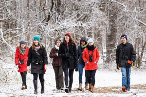 A group of students returning from a bird-watching class walk amid snow-dusted trees along a lakeshore path at Picnic Point at the University of Wisconsin-Madison during winter on Dec. 2, 2015.