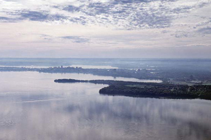 A pastel-colored sky is reflected in Lake Mendota in the foreground of this image featuring the dark outline of Frautschi Point, Picnic Point, and the Madison isthmus in an aerial view.